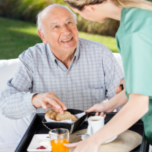 Serving foods to an elderly man.