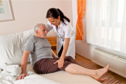 Helping an elderly man in the bed.